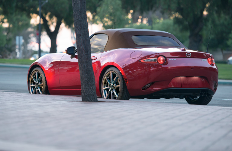 Exterior view of the rear of a red 2019 Mazda MX-5 Miata parked on a city street