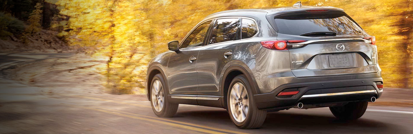 Exterior view of the rear of a gray 2019 Mazda CX-9 driving down a country road