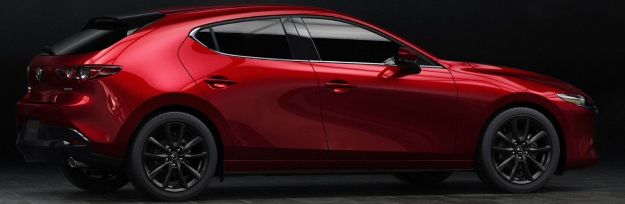 Exterior view of a red 2019 Mazda3 Hatchback parked against a black background