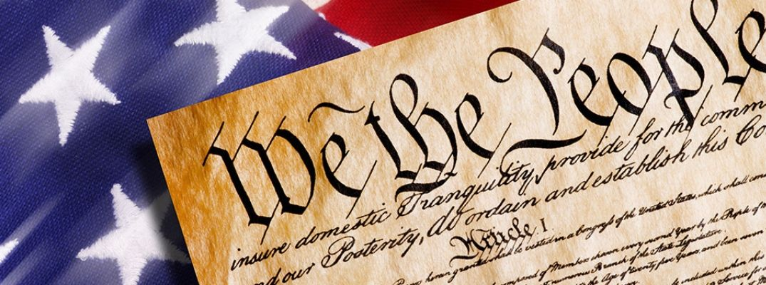 Image of the US Constitution laid out on an American Flag