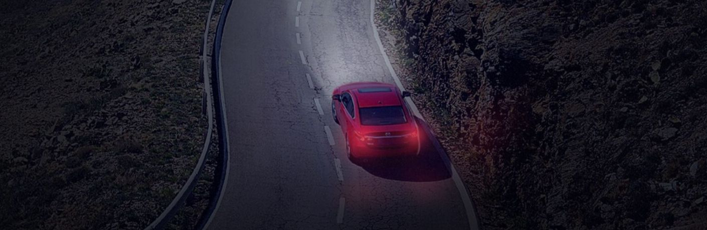 Exterior view of a red Mazda vehicle driving down a two-lane country road