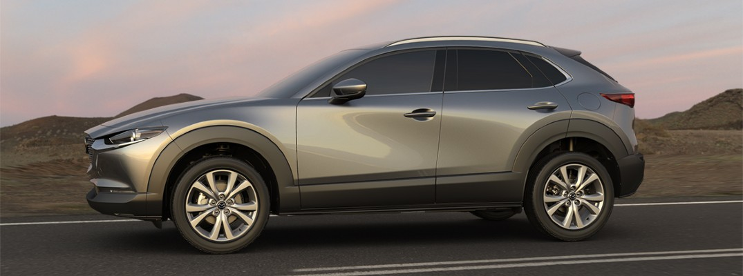 2020 Mazda CX-30 silver paint driving on desert road facing right at dusk