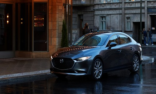 2020 Mazda3 dark gray paint parked on side of the road in the rain dark lighting
