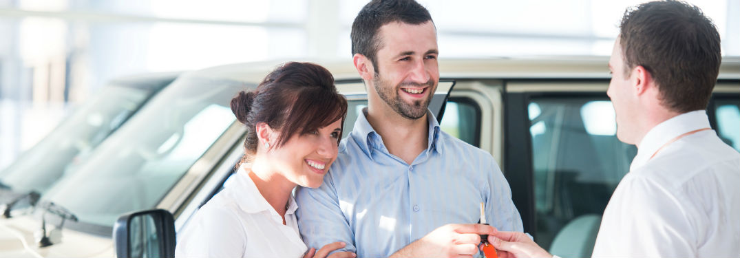 Smiling couple being handed keys to a car