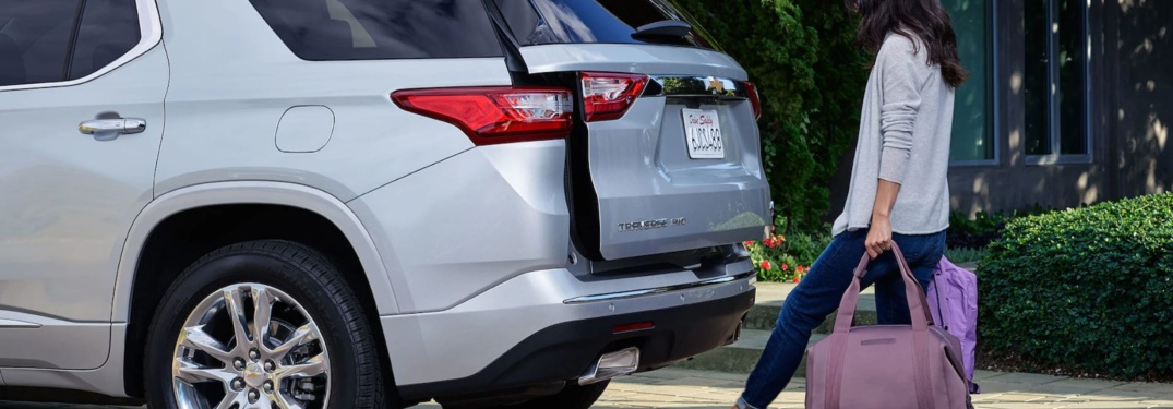 Woman loading gear into the back of a 2018 Chevy Traverse