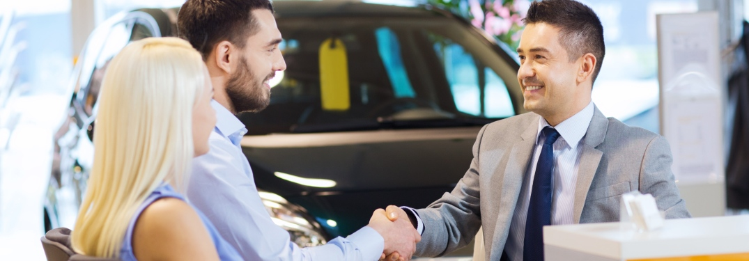 Young couple shaking hands with car salesman