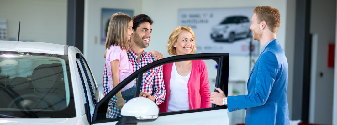 Polite looking delaership sales person discussing auto buying options with young couple in Christiansburg VA