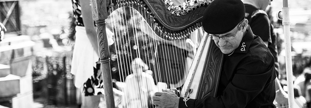 man playing harp in black and white