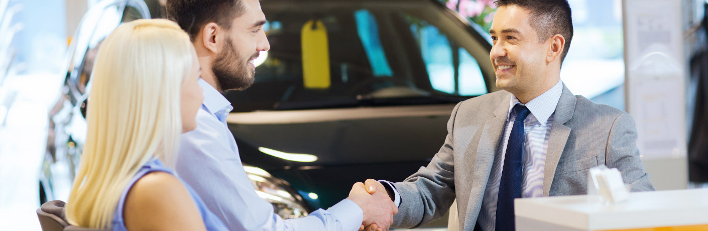 Couple shaking hands with a salesman at a dealership