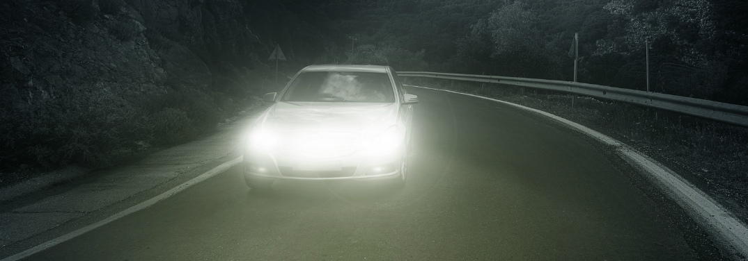 Car driving at night with bright headlights