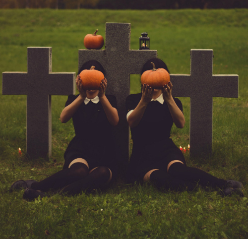Two girls dressed in black holding pumpkins over their faces in a cemetery