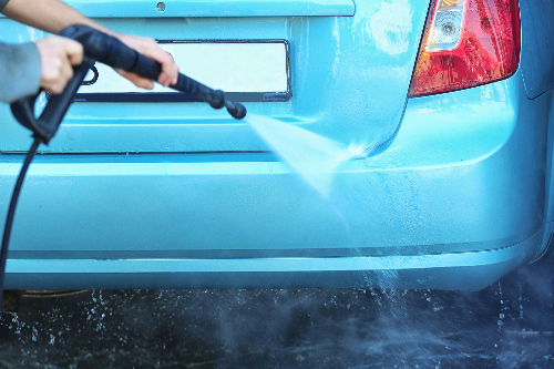 Man cleaning the bumper of a car with a pressure washer