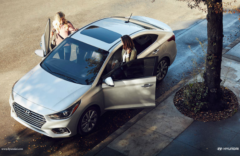 Two women getting into the front seats of the 2018 Hyundai Accent