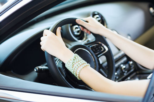 closeup of a woman with her hands on a steering wheel