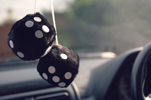 black fuzzy dice hanging in a car