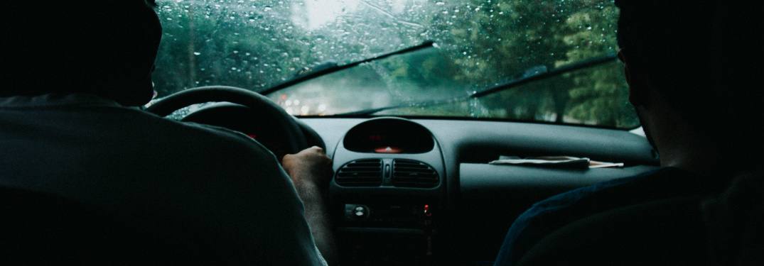 Two people riding in a car in the rain with a foggy windshield