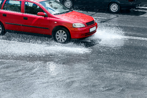 red car driving through a large puddle