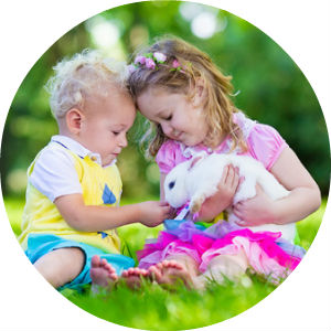 Circle image of two kids playing with a bunny in the grass
