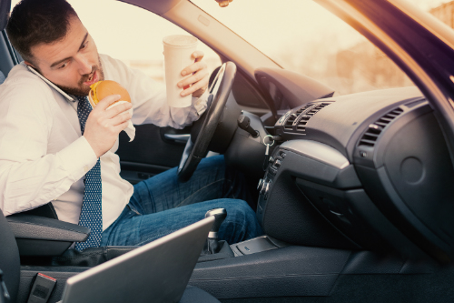 Man eating and drinking behind the wheel of a car