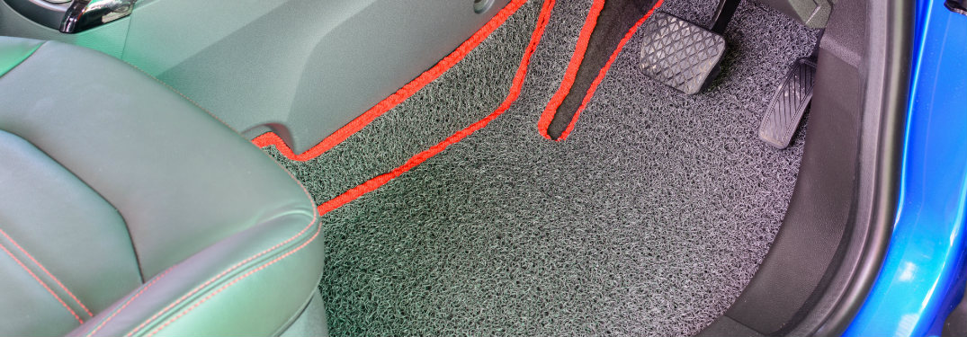 Grey floor mat with orange trim installed in a car