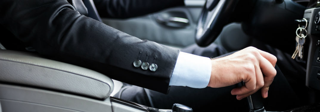 man with his hand on a vehicle shifting knob