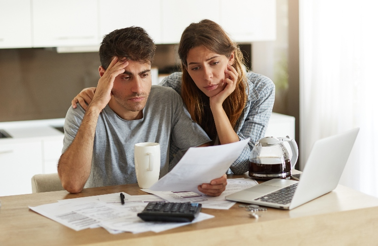 Unhappy Couple Looking at Paper