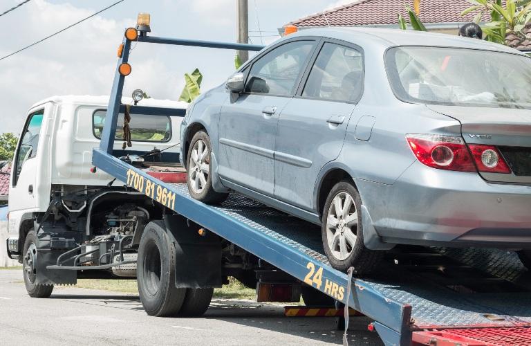 Vehicle being taken away on trailer