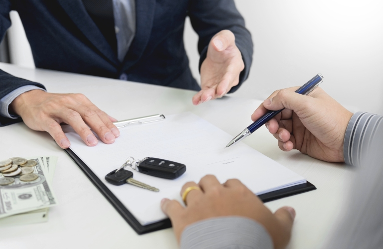 Person Signing Paperwork with Keys and Money