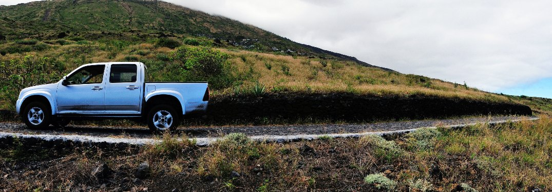 Pickup truck driving next to grassy mountain