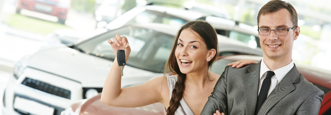 Happy couple with woman holding new car keys