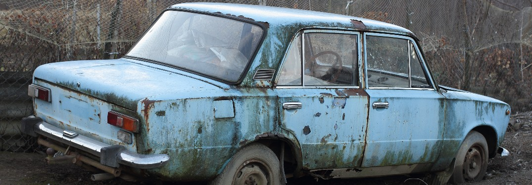 Rusty vehicle with leafless trees in background