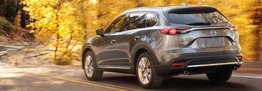 2019 Mazda CX-9 exterior rear view as it drives on highway surrounded by yellow leaves