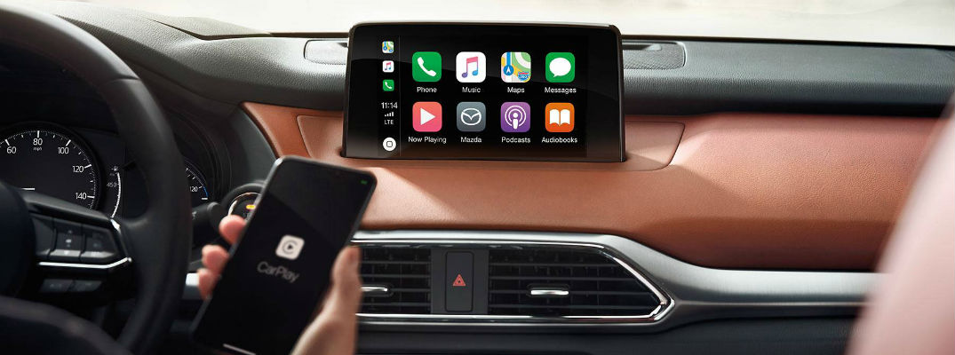 A photo of a person connecting an iPhone to a Mazda infotainment system.