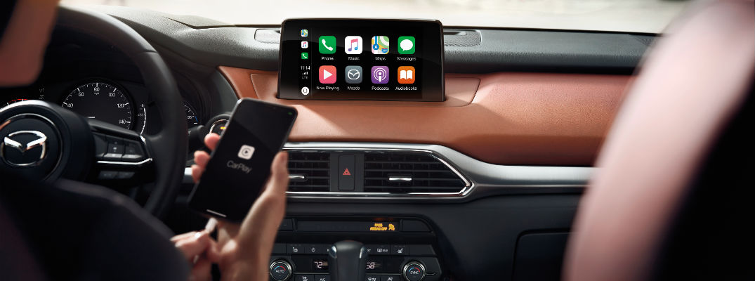 A photo of a person plugging their phone into the new Mazda infotainment system.