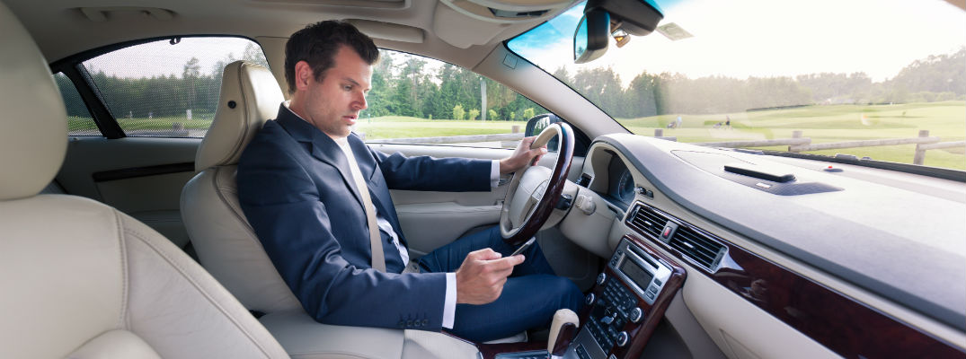 A stock photo of a person using their phone while driving.