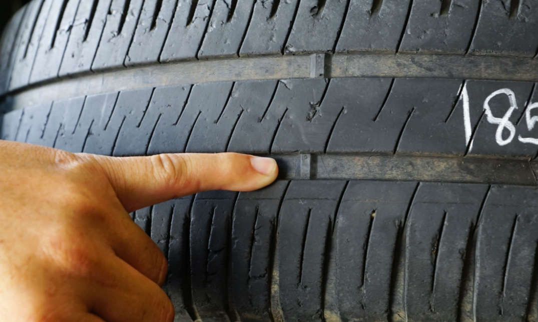 A stock photo of someone pointing at the warning indicator strip on a tire.