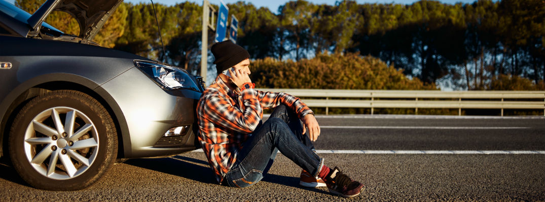 A stock photo of a person with a broken vehicle calling for help.
