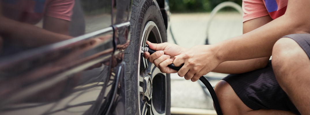 A stock photo of a person putting air in a car's tire.