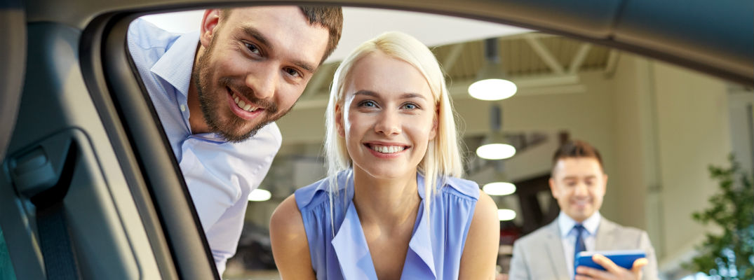 A stock photo of a young couple looking at a new car.