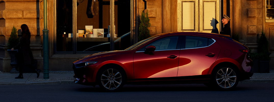 Red 2019 Mazda3 Hatchback Side Exterior on a City Street at Sunset