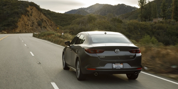 Gray 2019 Mazda3 Sedan Rear Exterior on a Mountain Road