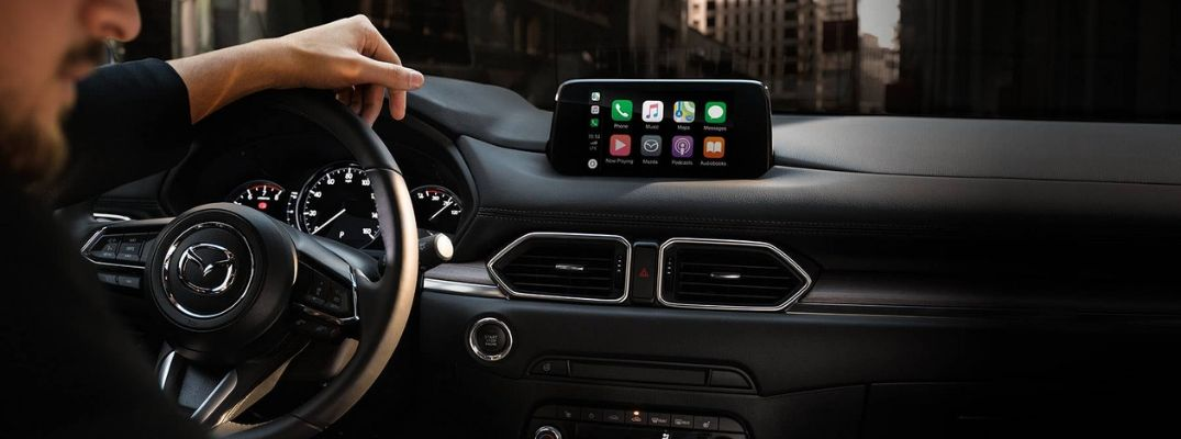 Man Behind the Wheel of a 2019 Mazda CX-5 with Apple CarPlay Menu on MAZDA CONNECT Touchscreen