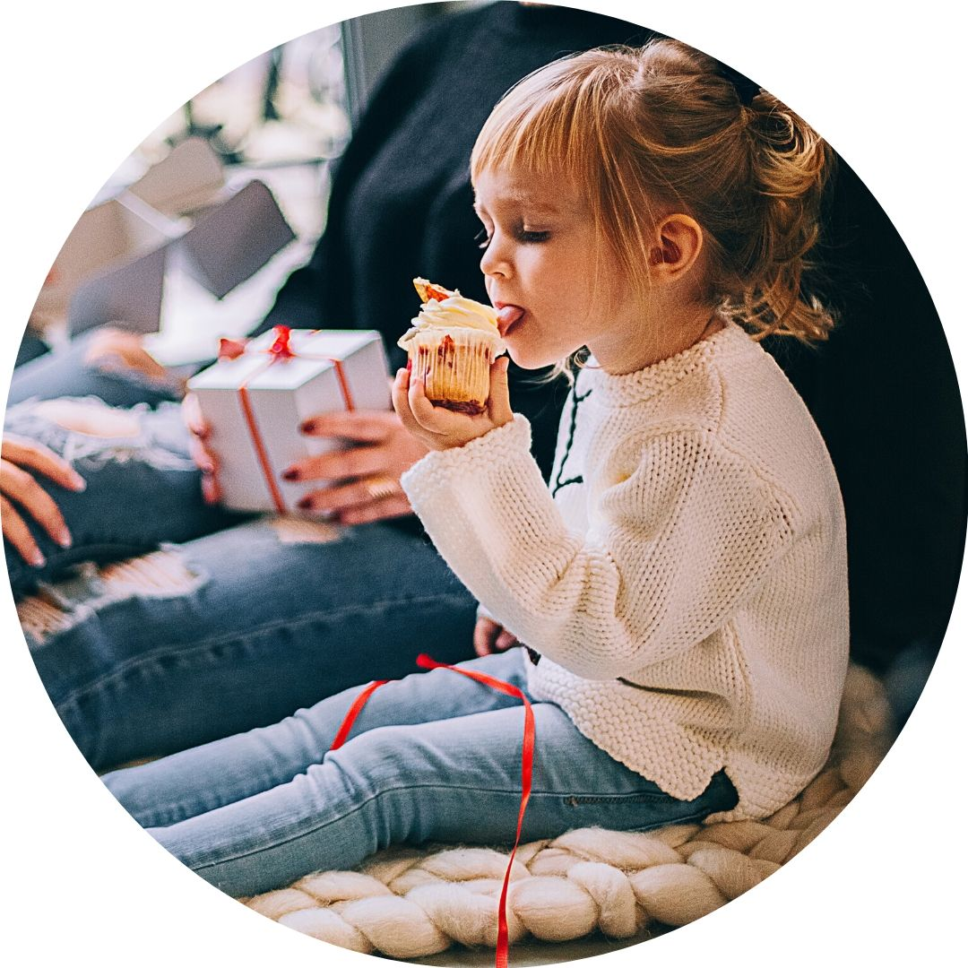 child eating cupcake in cozy winter clothes