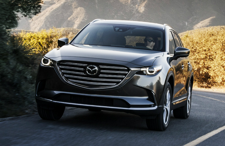 Grey 2018 Mazda CX 9 Driving On A Highway With Mountains In The Background