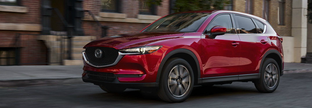 red 2018 mazda cx-5 parked in front of brick city building
