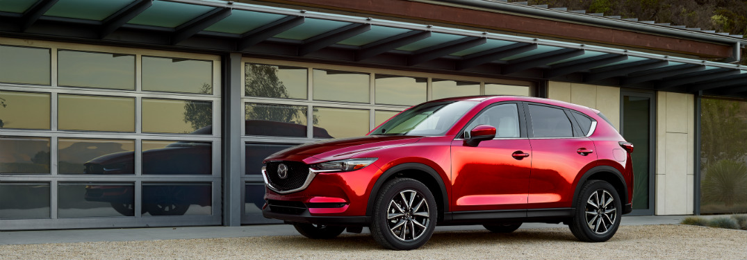 red 2018 mazda cx-5 in front of glass-panel garage