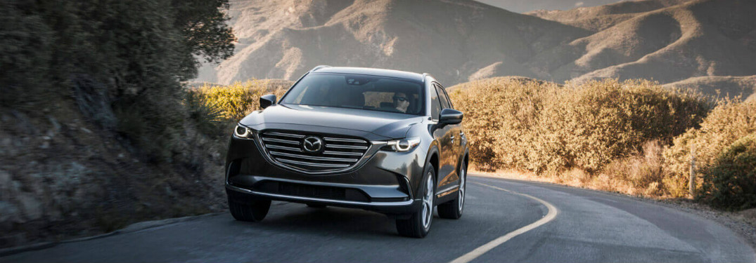 blue 2018 mazda cx-9 driving alone on mountain road