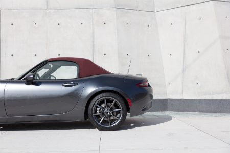 side view of rear of silver 2018 mazda miata mx-5 with top up in front of white wall