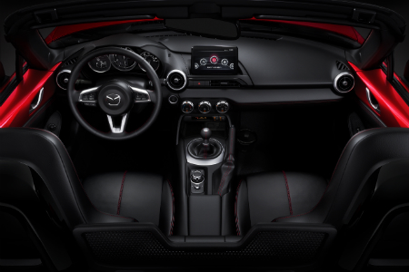 front interior of 2018 mazda miata mx-5 including seats, steering wheel and infotainment system