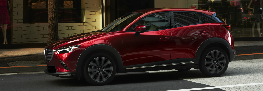 red 2019 mazda cx-3 parked on curb in city